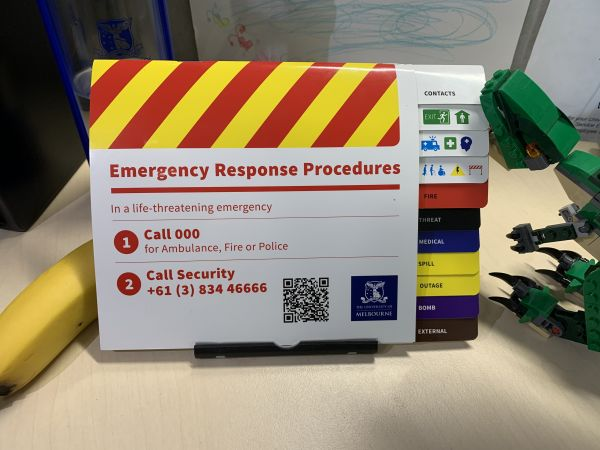 Emergency procedures flip chart on a desk near a phone and water bottle