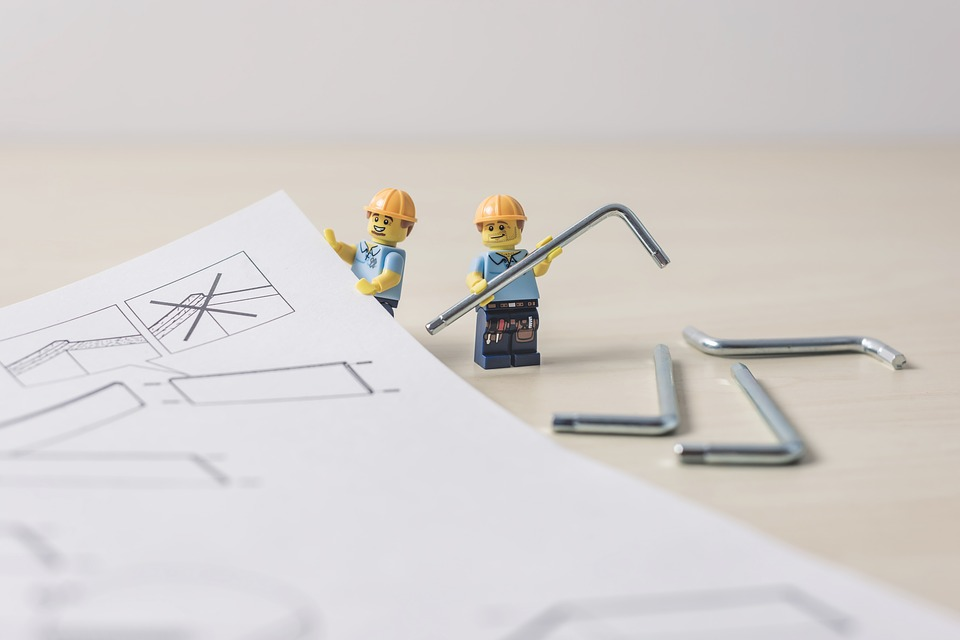 Lego constructions workers reading plans and holding allen keys