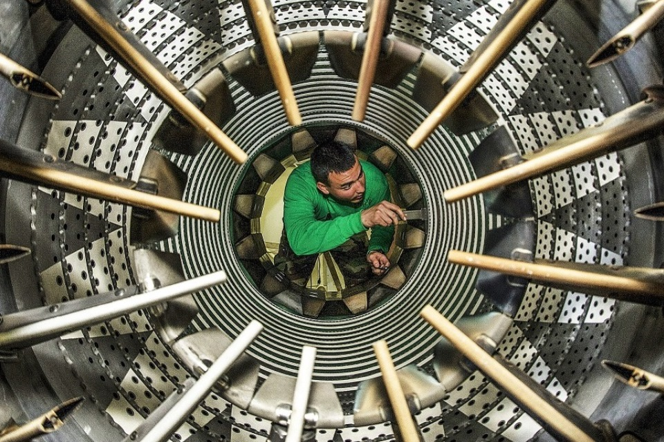 Man in green inspecting a large aircraft turbine