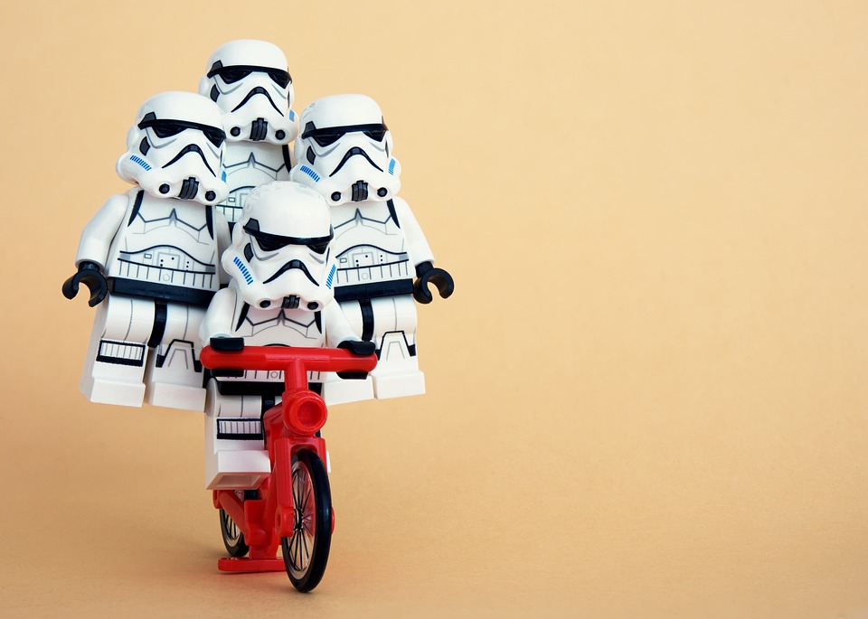 Four Lego Stormtroopers balancing on a red Lego bicycle