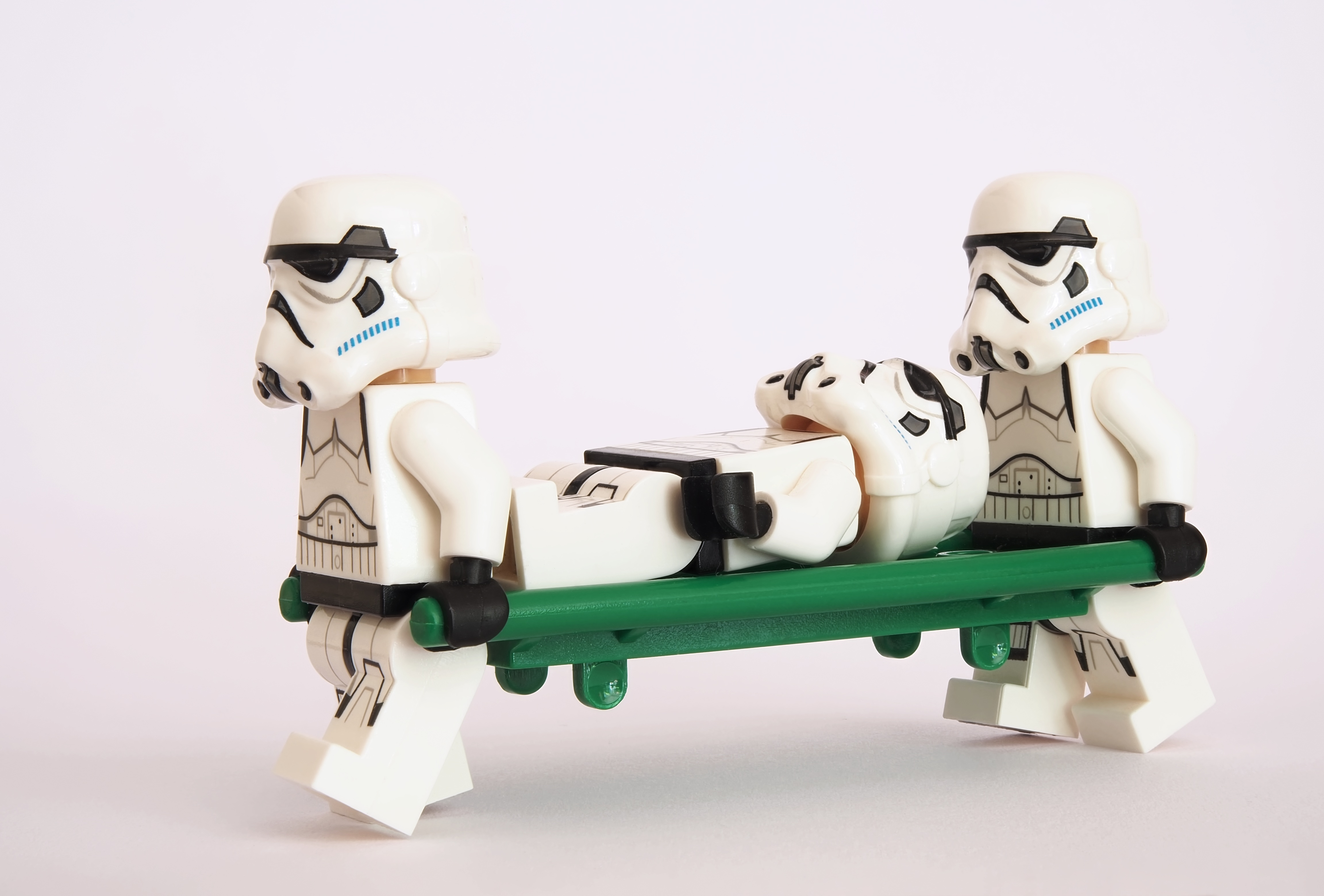 Two Lego Stormtrooper mini figures carrying a third Stormtooper on a green stretcher