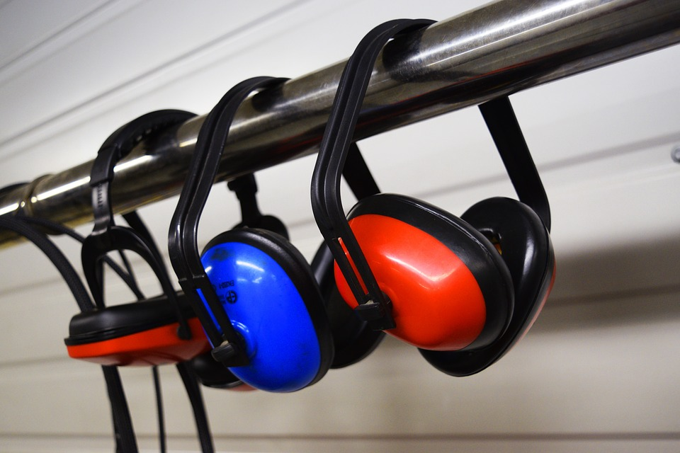 Three noise protection earmuffs hanging on a rail